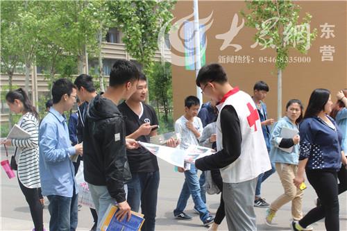 志愿者为来往师生发放宣传单页-东营职业学院青年志愿者开展无偿献